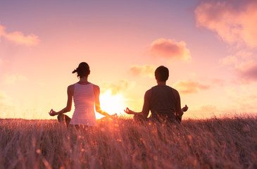 Man and woman meditating in a grass field at sunset.