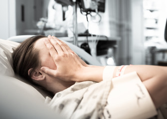 Young woman patient lying at hospital bed feeling sad and depressed worried. Disease feeling sick in health care and clinical attention concept