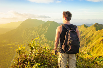 Adventure and exploring. Male hiker standing on a mountain peak looking at the view.  Location Hawaii.
