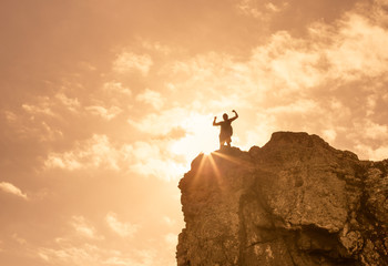 People, Victory, success, life goals concept. Hiker standing on edge of cliff raising his arms flexing.