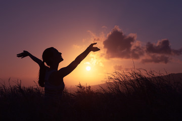 Young woman feeling happy and free in a beautiful, sunset nature setting.