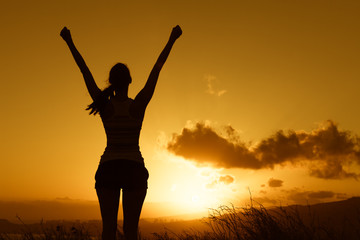 Happy victorious woman with her arms up facing the sunset.