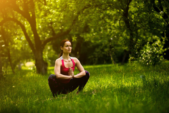 Woman practicing yoga concentrating in garland pose. In morning garden female doing Malasana. Toned image.