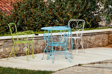 Chairs and a table in garden. Colorful steel chairs and a table standing in a beautiful garden at sunny day. Patio furniture. A set of three colored chairs and a small table set outdoor.