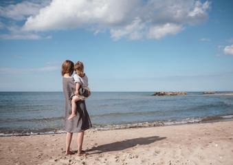 Am Strand trägt eine Mutter ihr Kind auf dem Arm und sie betrachten zusammen das Meer