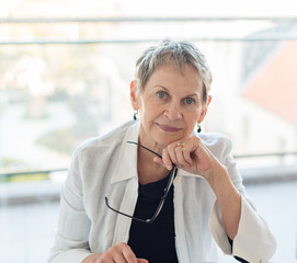 Portrait of professional looking older woman seated and holding glasses against window (selective focus)