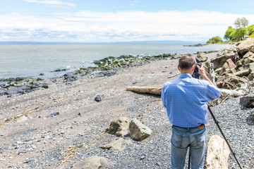 Photographer taking pictures of rocks and Saint Lawrence river in Saint-Irenee, Quebec, Canada in Charlevoix region with beach