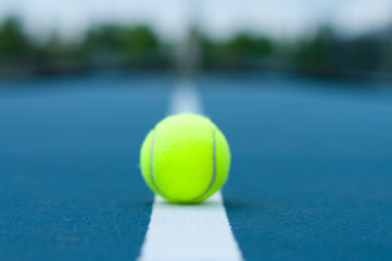 Tennis ball on tennis court with white line