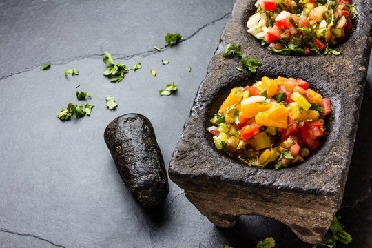 Famous mexican sauces salsas - pico de gallo, salsa bandera mexicana in stone mortars on gray slate background