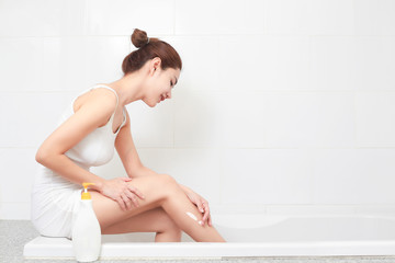 Young beautiful woman applying body lotion on her attractive legs in bathroom.