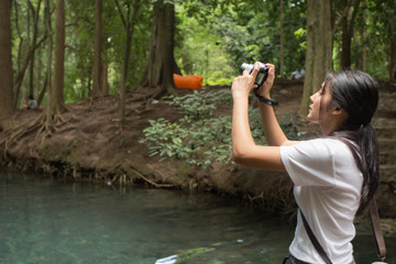 Asian woman taking photos in autumn forest