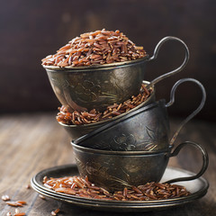 Red rice in vintage silver cups on an aged wooden background. Selective focus.