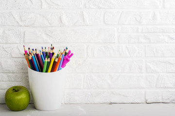 School background: a white brick wall with accessories, pencils, tetrads, scissors, an apple, pecans, a board for a substitute placed in front of her on the table. Selective focus.