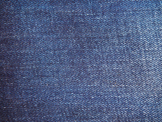 A full page of blue cotton material, denim fabric close-up. Macro photo texture of jeans. View of top on background texture close-up.