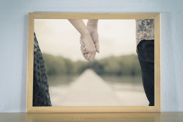 Couple holding hands in the picture frame placed on wood table. Love and Valentine concept.