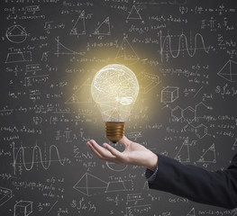 lightbulb brainstorming creative idea math formula on business hand.
