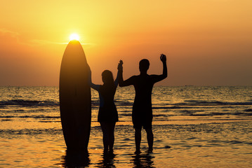 Couple standing with surfboard on the beach at Pattaya Thailand.