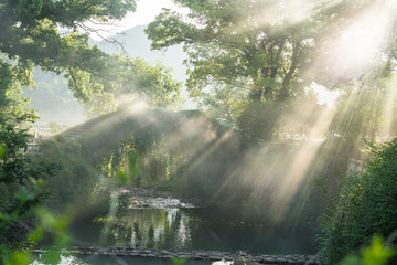sunlight through forest falling on stone bridge covered by green plants in small village of China.