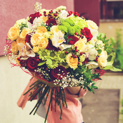 woman received a beautiful bouquet of red and beige roses, chrysanthemums and other flowers outdoors, toned image. Love and happiness concept