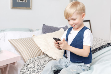 Smart small boy with mobile phone, seats on bed in bedroom. Technology concept