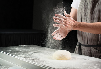 woman baker sprinkled flour on roll dough on a wooden board. Process of preparing pizza. Cooking time, cooking concept, selective focus