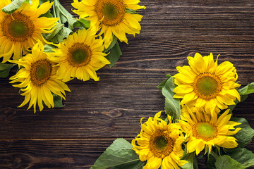 Yellow sunflowers on a dark wooden background. Copy space.