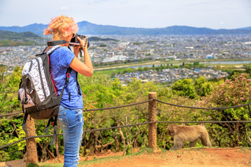 Nature woman photographer with camera takes picture of Kyoto skyline. Caucasian female with backpack shooting of Japanese macaque. Professional photographer in Iwatayama Monkey Park, Arashiyama, Japan