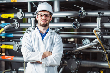 Portrait of a young smiling male worker in a white coat and helmet at a beer factory.