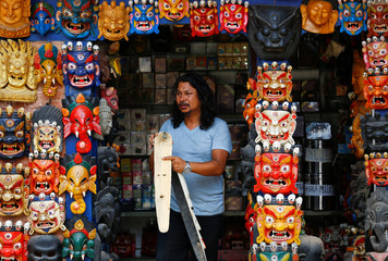 A shopkeeper walks out holding a mask from his souvenir shop in Bhaktapur