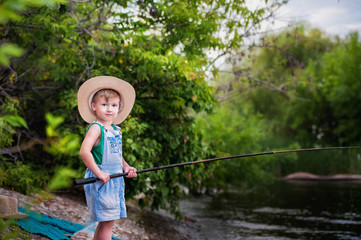 The grandson is fishing with his grandmother on the river bank. Fishermen with a fishing rod in the summer. A little boy with a grandmother puts a bait on a fishing rod, holds a fish. Grandmother and