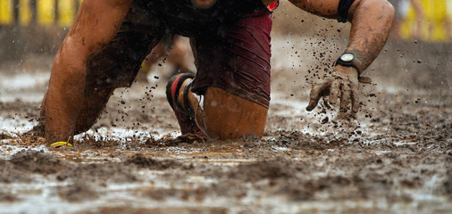Mud race runners.Crawling,passing under a barbed wire obstacles during extreme obstacle race Fototapete