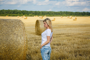 Attractive young woman near the stacks of straw