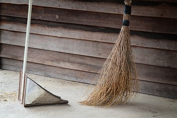 Broom and dustpan with wooden wall.