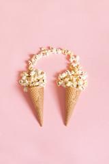 Popcorn in ice cream cones on pink background. Top view. Vertical.