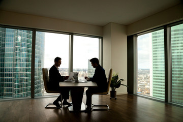 Two businessmen negotiating sitting at conference table in modern office interior with big full-length window and city buildings outside, business partners working together, preparing business offer