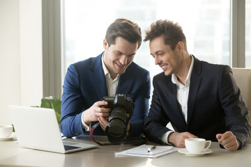 Happy businessman holding new professional camera, showing photographs to smiling colleague, partners viewing discussing pictures of business object, satisfied client looking at photos for project ads