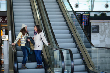 Two young women with small luggage on the escalator at the airport.
