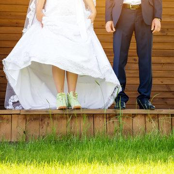 Funny beautiful wedding couple. Bride wearing green running shoes. Runaway Bride, close up.