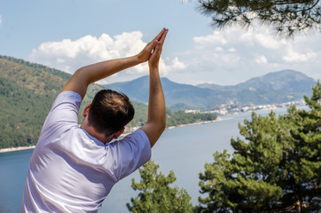 Young beautiful smiling man doing yoga exercises on kerimat on top of mountain looking at the sea resting and meditating