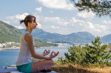 A woman in the lotus position sits and meditates on top of the mountain on the background of the sea