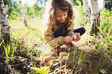 happy child girl picking wild mushrooms on the walk in summer or autumn forest
