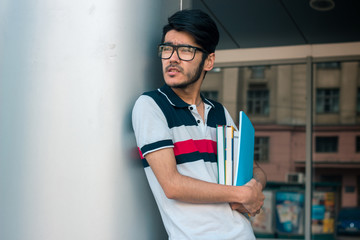 handsome student with books in hands wears a glasses and looks aside