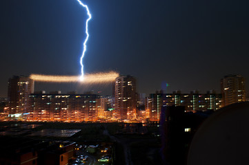 OMSK, RUSSIA - August 7, 2012: Thunderstorm in the city, lightning struck in the power line between the houses