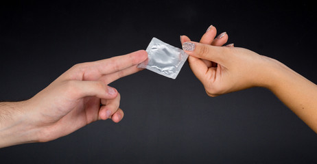 a man passes a condom to a woman