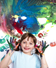 happy little girl playing with colors on a white paper