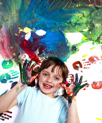 portrait of a happy school girl playing with water colors
