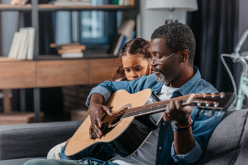 man playing guitar with daughter at home