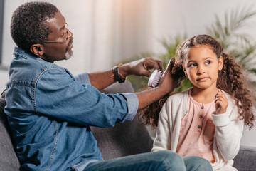African american man combing daughter
