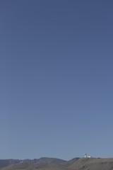 Radio Telescope on a Sierra Nevada mountain ridge pointing at a clear blue sky