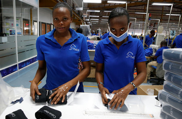 Kenyan workers pack men's underwear at the Hela intimates export processing zone limited factory in Athi River, near Nairobi